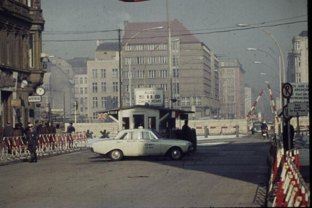 Kontrola  w Checkpoint Charlie z pojazdem policji wojskowej USA, w tle przejście graniczne Friedrichstrasse