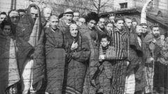 Wyzwoleni więźniowie obok wartowni (Blockführerstube) przy bramie do obozu macierzystego