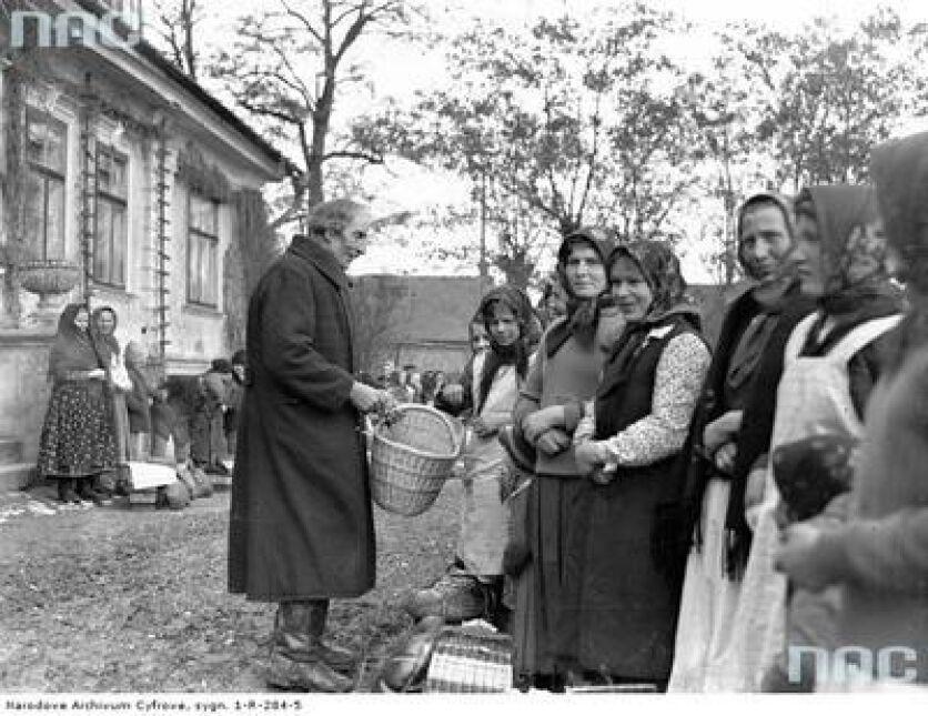 Kościelny podczas zbierania ofiar w naturze za poświęcenie pokarmów w Tomaszowicach