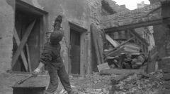 """Ppor. Jerzy Siwiec """"Jur"""", z kompanii """"Anna"""" batalionu """"Gustaw"""", przed kamienicą na ulicy Ślepej na Starówce, rzucający granatem Stielhandgranate-24 ponad """"bramką"""" w kierunku pozycji niemieckich przy pl. Zamkowym"""
