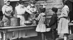 Podczas epidemii grypy wolontariusze w maskach karmią dzieci dotkniętych rodzin