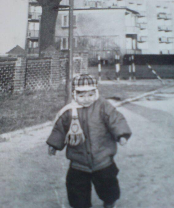 Zdjęcie z dzieciństwa Patryka Jakiego, który stoi pod blokiem