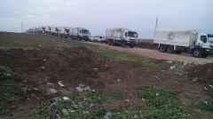 Ciężarówki z pomocą humanitarną na rogatkach miasta
