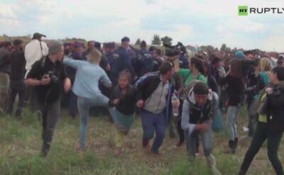 Imigranci uciekają przed policją. Operatorka kamery kopie i podstawia im nogę